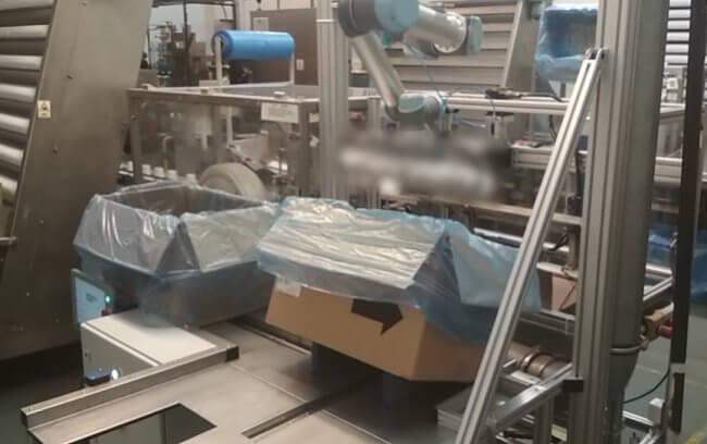 Stacja pakująca produkty do kartonów wykorzystująca cobota Universal Robots